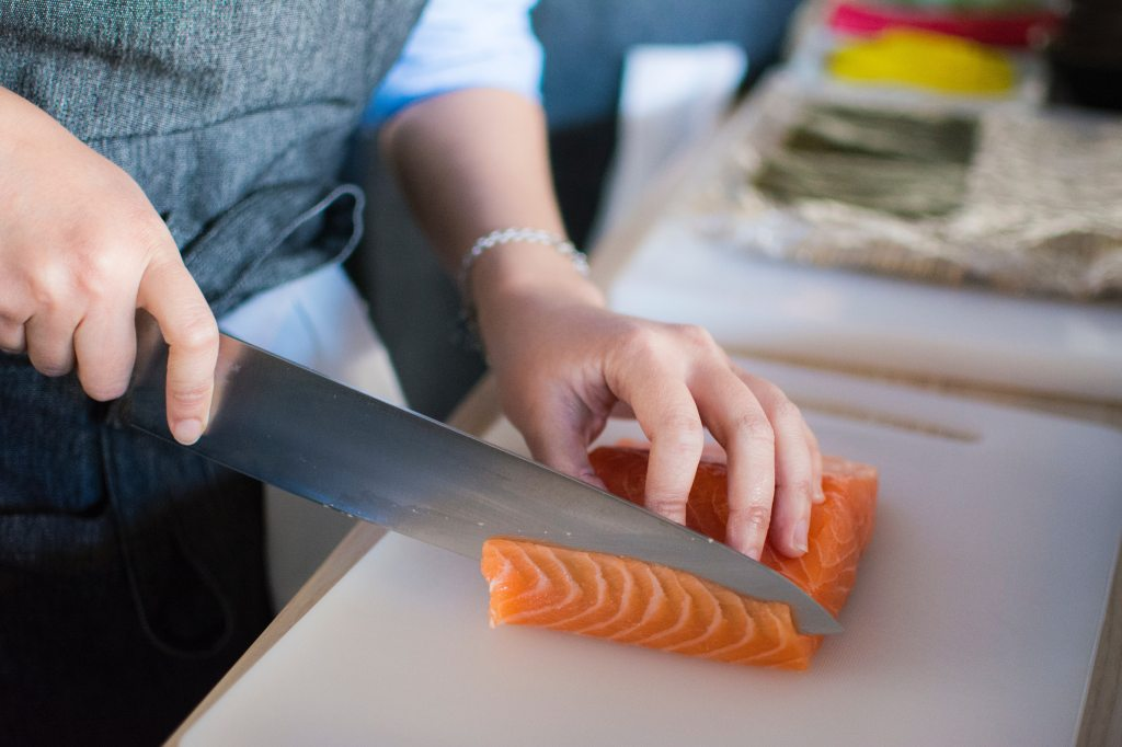 A chef preparing raw salmon. Photo by Huy Phan.