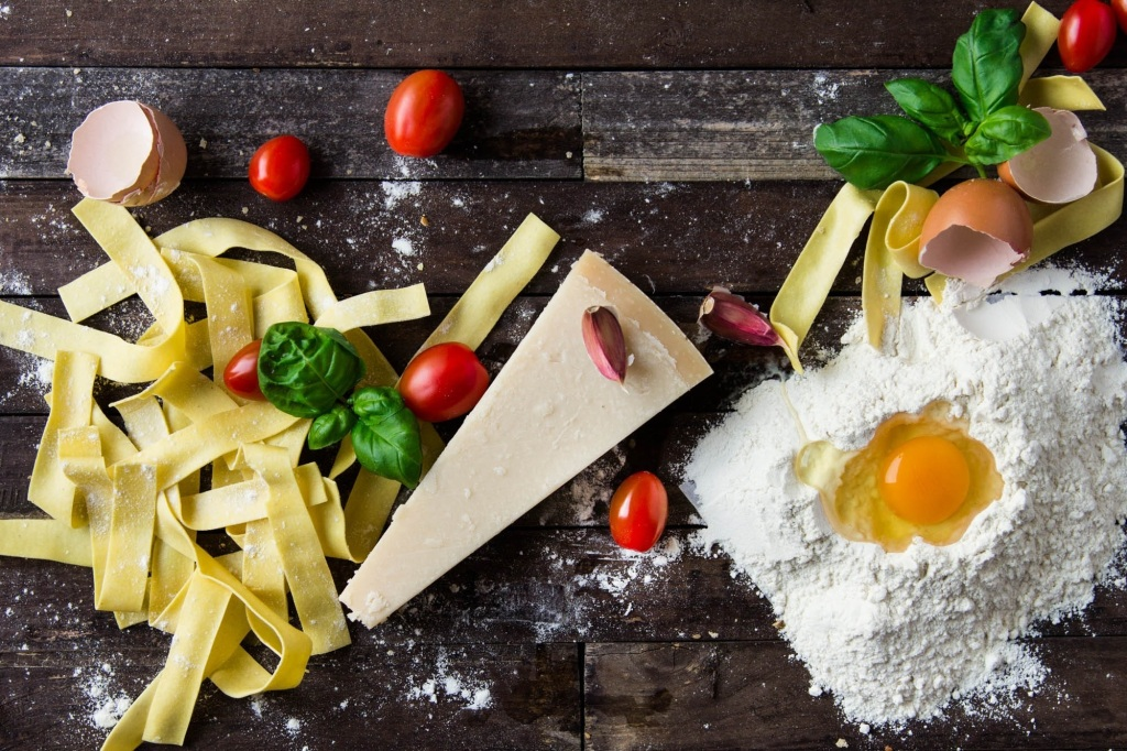 Eggs, cheese, pasta, tomatoes and basil on a wooden table top